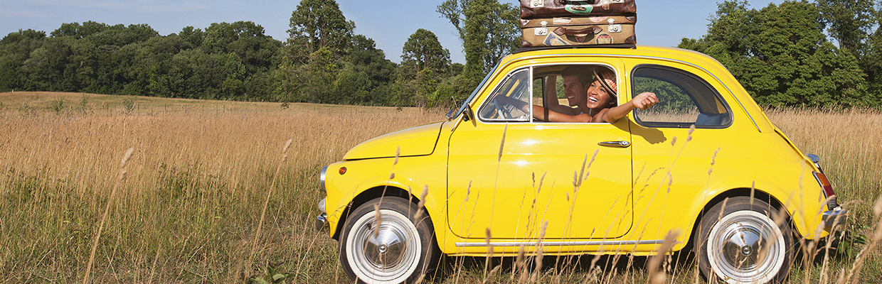 A woman driving a yellow car with suitcases on top; image used for HSBC faster access, more control page.