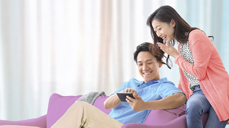 Happy couple is using mobile; image used for HSBC Amanah Balance Conversion Plan page.