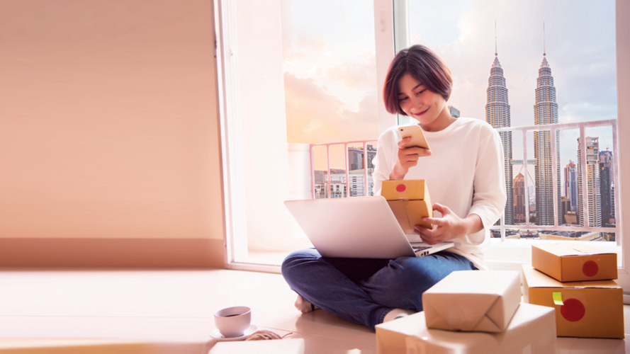 Woman with laptop holding package and mobile phone; image used for HSBC Amanah Everyday Global Account-i.